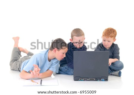 Young boys casual dressed, doing homework on laptop.  White background, studio shot.