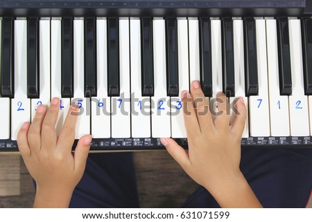 Young boys hands playing music on electronic piano or keyboard