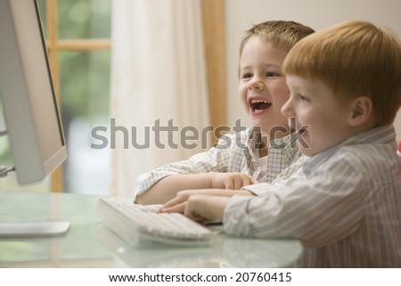 Young boys having fun at the computer - stock photo