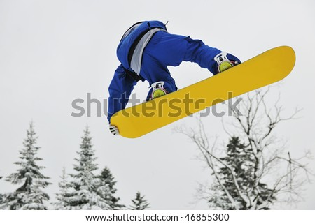 young boys jumping in air ind showing trick with snowboard at winter season - stock photo