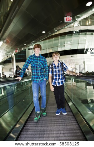 young boys on a moving staircase at the airport - stock photo