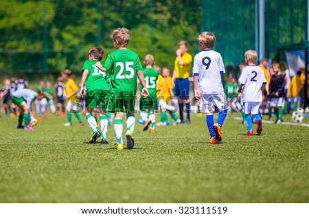 Young boys play football soccer match. Players walk across the soccer field. Two teams. - stock photo