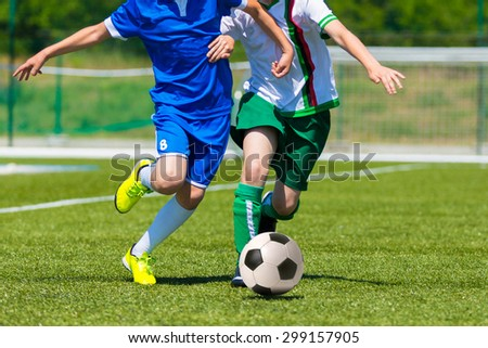 young boys playing football soccer game. Running players in blue and white uniforms - stock photo