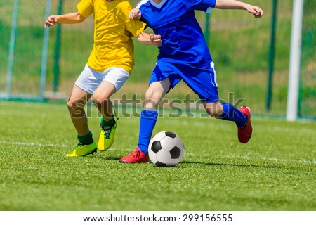 young boys playing football soccer game. Running players in blue and yellow uniforms - stock photo