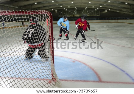 Young Boys Playing Hockey in front of the Goalie Net - stock photo