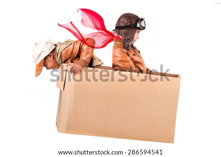 Young boys playing in a cardboard box isolated in white - stock photo