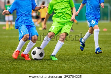 Young boys playing youth soccer football game - stock photo