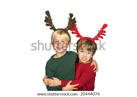 Young boys wearing antlers excited for Christmas and hugging with big toothless smile - stock photo