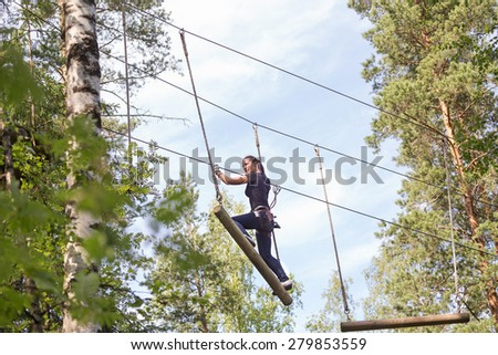 Young brave woman climbing in a adventure rope park - stock photo