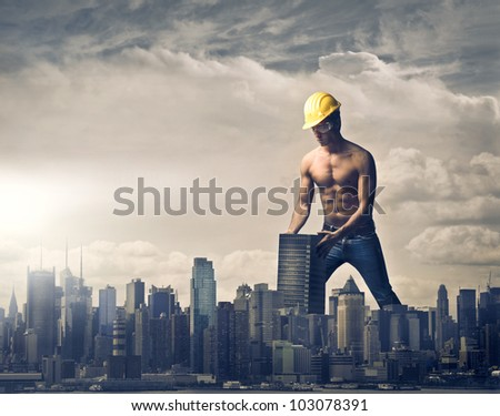 Young brawny worker settling a skyscraper in the skyline of a big city - stock photo