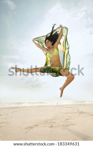 young Brazil supporter jumping for joy with Brazil flag  - stock photo