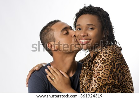 Young Brazilian couple. The woman is seated on her husband's lap, and he's kissing her on her face. She is looking for the camera and smiling.