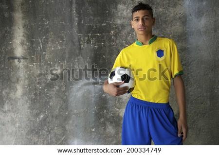 Young Brazilian footballer in team Brazil colors kit holding soccer ball against concrete favela wall - stock photo