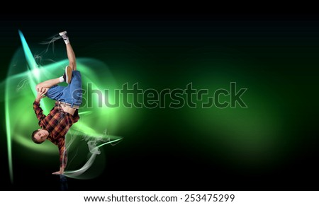 Young breakdancer performing a hand stand on color background
