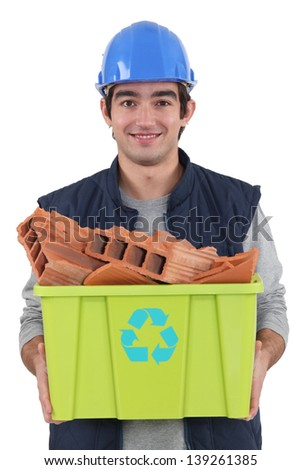 young bricklayer carrying recycling tub full of red bricks - stock photo
