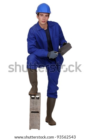young bricklayer with leg resting on block of concrete holding trowel - stock photo
