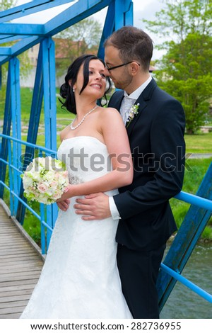 young bridal couple standing together on a blue bridge