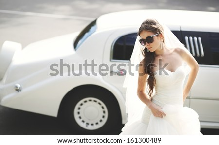 Young bride against limo. Hot summer day. Wedding picture. - stock photo