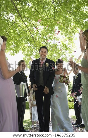 Young bride and groom being showered with flower petals by guests - stock photo