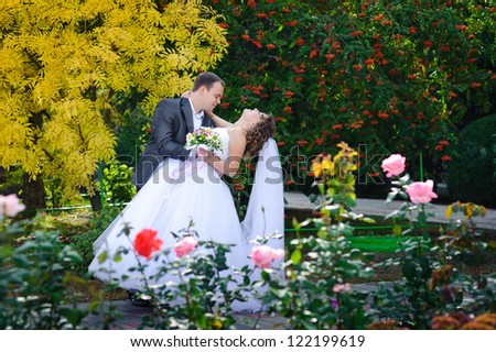 young bride and groom in the park, a wedding bouquet, wedding dresses - stock photo