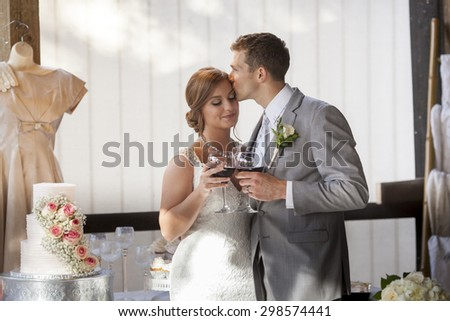 Young bride and groom kissing after toast - stock photo