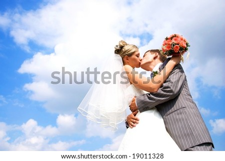 young bride and groom kissing against blue sky with clouds - stock photo