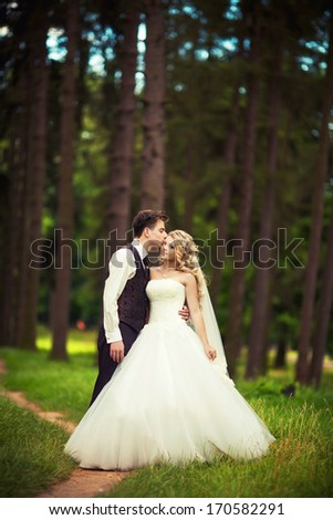 Young Bride and groom posing in park - stock photo