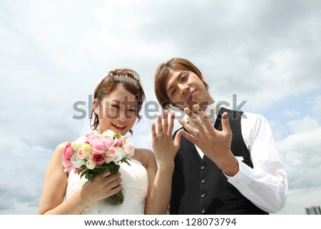 Young bride and groom showing rings against cloudy sky
