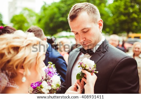 young bride gives her groom a small beautiful bouquet - stock photo