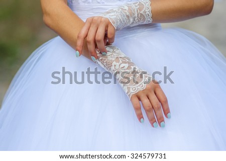 Young bride hands with beautiful manicure dress gloves. - stock photo