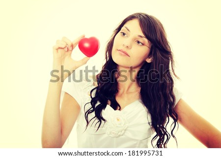 Young bride holding heart, isolated on white background - focus on heart - stock photo