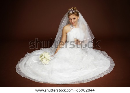 Young bride in a white dress sitting on a brown background - stock photo