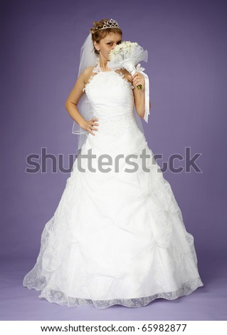 Young bride in a white dress with a bouquet on purple background - stock photo