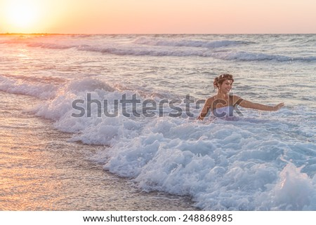 Young bride in a white wedding dress, enjoys a swim in the ocean waters, in late summer, at dusk. - stock photo