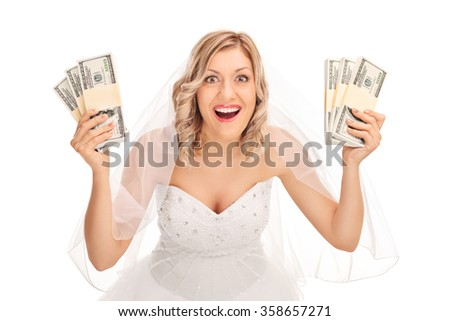 Young bride in a white wedding dress holding few stacks of money isolated on white background - stock photo