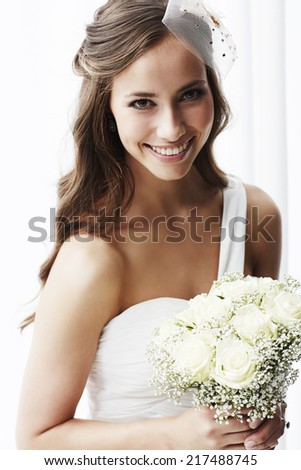 Young bride in wedding dress holding bouquet, portrait  - stock photo