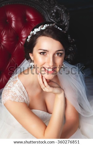 Young bride is sitting in an armchair.Beautiful Bride Portrait wedding makeup, wedding hairstyle, Wedding dress. Wedding decoration. soft selective focus. gorgeous young bride at interior - stock photo