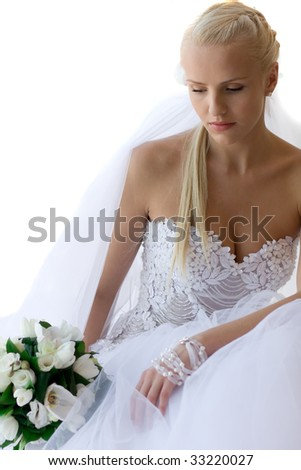 Young bride looking down, with bouquet - stock photo
