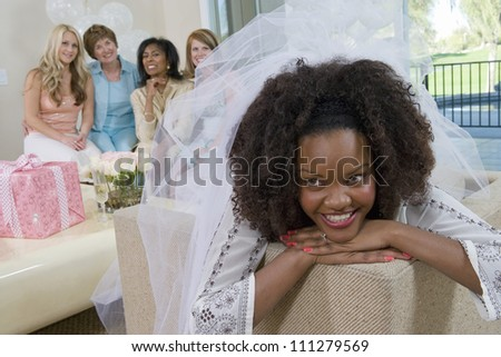 Young bride lost in thoughts with friends in the background