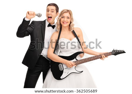 Young bride playing electric guitar and the groom signing on a microphone behind her isolated on white background - stock photo