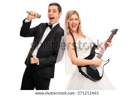 Young bride playing guitar and a young groom singing on microphone isolated on white background - stock photo