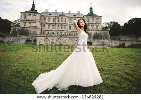 young bride posing against castle in west Ukraine - stock photo