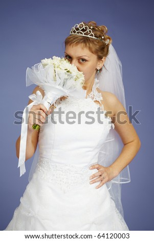 Young Bride smell the flowers on a blue background - stock photo