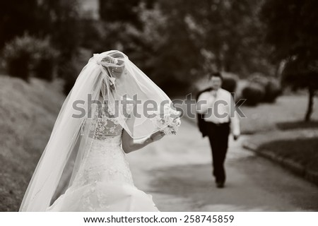 Young bride spinning around with veil. Wedding couple together.  - stock photo