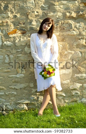 young bride standing at the wall - stock photo