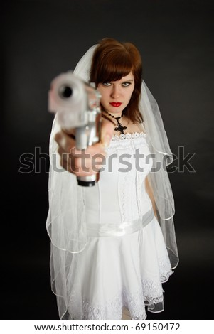 Young bride threatens us with a gun on black background - stock photo
