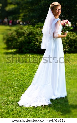 Young bride walking in park. Vibrant colors. - stock photo