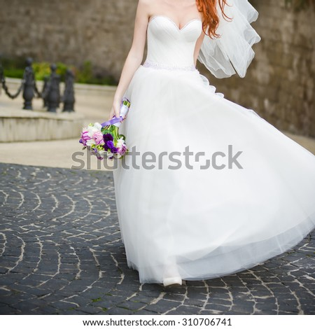 young bride with large breasts is holding a wedding bouquet before wedding ceremony in various poses near old castle - stock photo