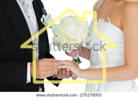 Young bridegroom putting on the wedding ring on his wifes finger against house outline - stock photo