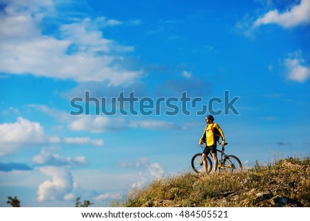 young bright man on mountain bike on a rural background